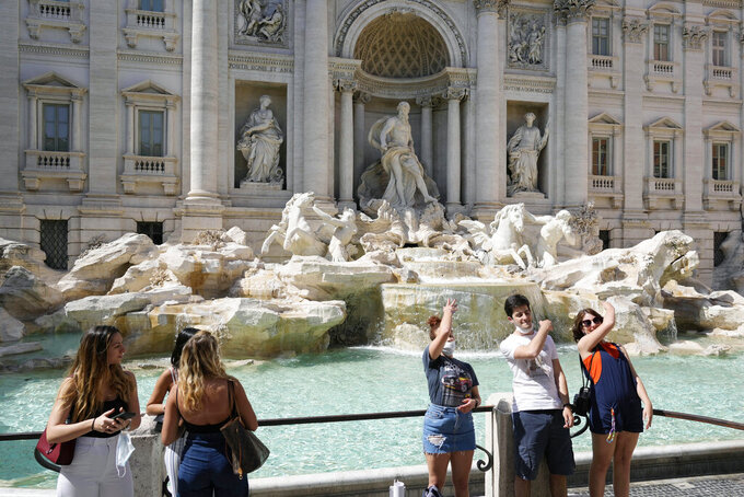 FILE - In this Friday, June 4, 2021 file photo, tourists throw their coins into the Trevi fountain as a wish to come back to the eternal city, in downtown Rome. The European Union is recommending that member countries start lifting restrictions on tourists from the United States. EU members agreed Wednesday, June 16, 2021 to add the U.S. to the list of countries in whose cases restrictions on non-essential travel should be lifted. (AP Photo/Gregorio Borgia, File)