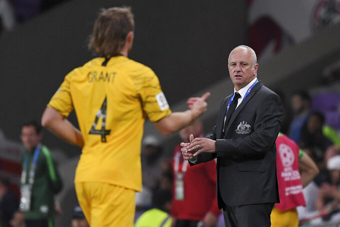 FILE - In this Jan. 25, 2019, file photo, Australia's head coach Graham Arnold, right, looks at Australia's defender Ryan Grant during the AFC Asian Cup quarterfinal soccer match between United Arab Emirates and Australia at Hazza Bin Zayed Stadium in Al Ain, United Arab Emirates. After 18 months without a game, the gathering of Australian players in Dubai ahead of next month's World Cup qualifiers feels like a family reunion for head coach Graham Arnold.(AP Photo/Hassan Ammar, File)