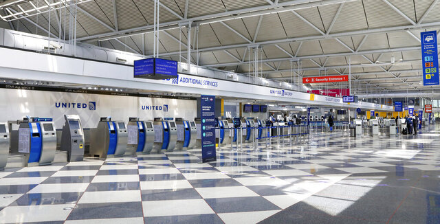 Rows of United Airlines check-in counters at O'Hare International Airport in Chicago are unoccupied on June 25, 2020, amid the coronavirus pandemic. United is sending layoff warnings to 36,000 employees, nearly half its U.S. staff, the airline announced Wednesday, July 8. (AP Photo/Teresa Crawford)
