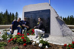 John Williams, of Peru, Ind., left, and his sisters, Maria McCauley, of Branson, Mo., center, and Susie Linale, of Omaha, Neb., pose at a monument to honor the military passengers of Flying Tiger Line Flight 739, Saturday, May 15, 2021, in Columbia Falls, Maine. Their father, SFC Albert Williams, Jr., was among those killed on the secret mission to Vietnam in 1962. (AP Photo/Robert F. Bukaty)