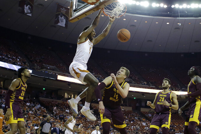 Texas forward Royce Hamm Jr. (5) scores over Central Michigan forward David DiLeo (14) during the second half of an NCAA college basketball game, Saturday, Dec. 14, 2019, in Austin, Texas. (AP Photo/Eric Gay)