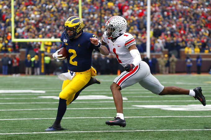 Michigan quarterback Shea Patterson (2) tries to avoid Ohio State cornerback Jeff Okudah (1) in the first half of an NCAA college football game in Ann Arbor, Mich., Saturday, Nov. 30, 2019. (AP Photo/Paul Sancya)