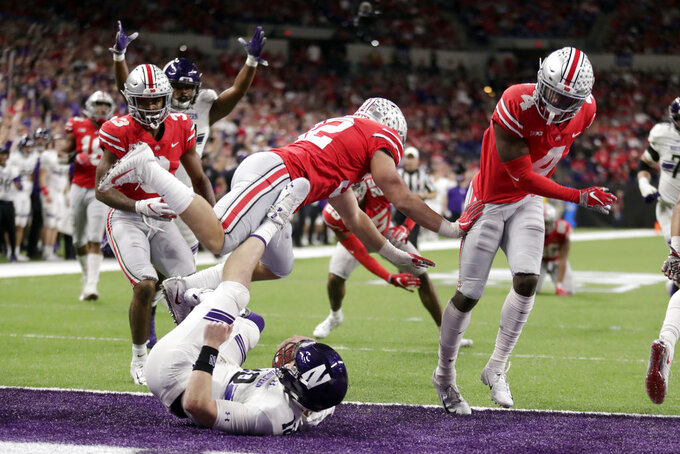Northwestern quarterback Clayton Thorson, bottom, falls into the end zone at the end of a touchdown during the second half of the Big Ten championship NCAA college football game against Ohio State, Saturday, Dec. 1, 2018, in Indianapolis. (AP Photo/Michael Conroy)
