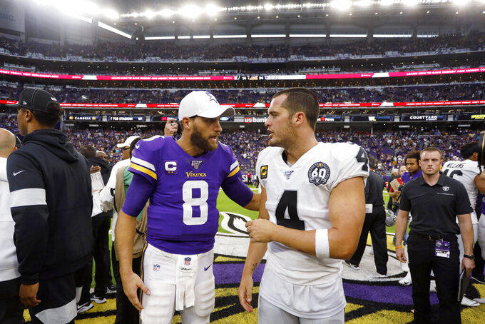 Minnesota Vikings quarterback Kirk Cousins, left, talks with Oakland Raiders quarterback Derek Carr after an NFL football game, Sunday, Sept. 22, 2019, in Minneapolis. The Vikings won 34-14. (AP Photo/Bruce Kluckhohn)