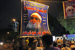 FILE — In this Sept. 11, 2011 file photo, Egyptian followers gather under a poster with a picture of Sheik Omar Abdel-Rahman, the Egyptian cleric jailed in the United States for planning a campaign of bombings. Arabic reads