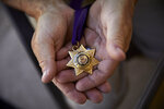 In this April 9, 2019, photo, Grant Whitus holds the Jefferson County Sheriff's Star at his home in Lake Havasu City, Ariz. Whitus received the award for his actions on several incidents while with the Jefferson County Regional SWAT team, including Columbine High School. Whitus' marriage fell apart a year after he led his SWAT team into Columbine High School's library, where he was the first to find the dead children's bodies. (AP Photo/John Locher)