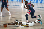 New Orleans Pelicans guard Jrue Holiday (11) dives for the ball against Washington Wizards guard Jerian Grant (22) during the second half of an NBA basketball game Friday, Aug. 7, 2020, in Lake Buena Vista, Fla. (Kim Klement/Pool Photo via AP)