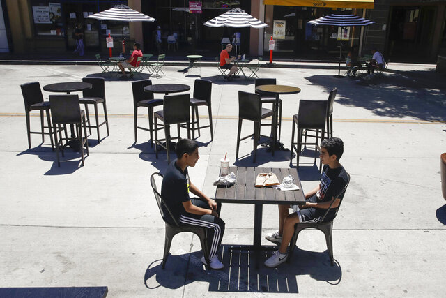 FILE - In this July 18, 2020 file photo, young patrons eat a meal on a closed-off street near sparsely sat tables in Burbank, Calif. California's unemployment rate has fallen to 11.4% in August. The Employment Development Department says the state added 101,900 jobs in August. Most of those were government jobs, including temporary positions for the U.S. Census. California lost more than 2.6 million jobs in March and April because of the coronavirus. (AP Photo/Marcio Jose Sanchez, File)