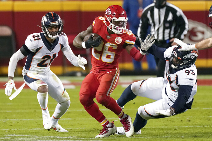 FILE - In this Sunday, Dec. 6, 2020 file photo, Kansas City Chiefs running back Le'Veon Bell (26) runs as Denver Broncos cornerback A.J. Bouye (21) and Denver Broncos defensive end Dre'Mont Jones (93) defend in the first half of an NFL football game in Kansas City, Mo. Le'Veon Bell and Tampa Bay Buccaneers Leonard Fournette go from losing squads to Super Bowl. (AP Photo/Charlie Riedel, File)