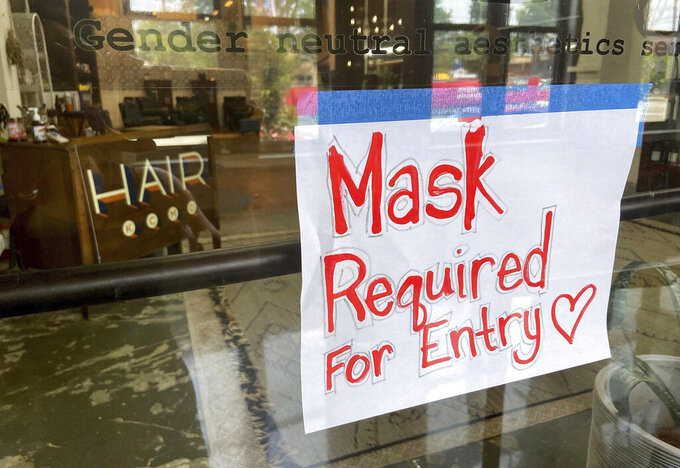 FILE - This July 2021 file photo shows a sign on the door of a hair salon informing patrons that masks are required to be in the business in Kansas City, Mo. St. Louis County's top elected official insisted Wednesday, July 28, 2021 that a mask mandate remained in place even though the county commission voted to overturn it. Across the state, meanwhile, Kansas City issued its own order in an effort to stem a rise in COVID-19 cases that is straining hospitals, leading to an immediate threat of a lawsuit.(Jill Toyoshiba/The Kansas City Star via AP, File)