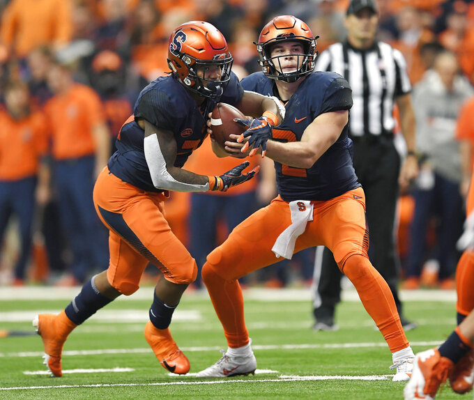 Syracuse quarterback Eric Dungey, right, fakes a hand off to running back Moe Neal during the second half of an NCAA college football game against Louisville in Syracuse, N.Y., Friday, Nov. 9, 2018. (AP Photo/Adrian Kraus)