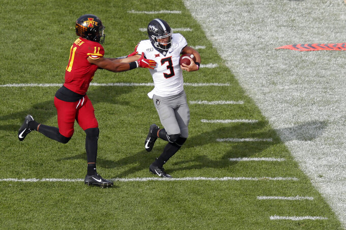 Iowa State defensive back Lawrence White, left, forces out Oklahoma State quarterback Spencer Sanders during the first half of an NCAA college football game, Saturday, Oct. 26, 2019, in Ames, Iowa. (AP Photo/Matthew Putney)