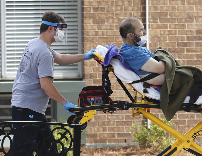 A Southeast Ambulance employee arrives with a patient at PruittHealth Grandview nursing home where at least 10 patients who were previously tested presumptive positive for COVID-19 have passed away on Wednesday, April 8, 2020, in Athens. The facility continues to operate at an alert code red status following enhanced infectious disease protocol despite the deaths. (Curtis Compton/Atlanta Journal-Constitution via AP)