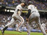 San Francisco Giants' Buster Posey celebrates with first base coach Jose Alguacil after hitting a grand slam during the 10th inning of a baseball game against the Milwaukee Brewers Friday, July 12, 2019, in Milwaukee. (AP Photo/Morry Gash)