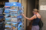 A woman shops for postcards in town of Sóller in the Balearic Island of Mallorca, Spain, Monday, July 27, 2020. Britain has put Spain back on its unsafe list and announced Saturday that travelers arriving in the U.K. from Spain must now quarantine for 14 days. (AP Photo/Joan Mateu)