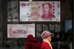 Women walk by a bank window panel displaying the security markers on the latest 100 Yuan notes in Beijing, Monday, Feb. 18, 2019. China's policy ministry says it investigated 380 online lenders and froze $1.5 billion in assets in a crackdown following an avalanche of scandals in the huge but lightly regulated industry. (AP Photo/Andy Wong)