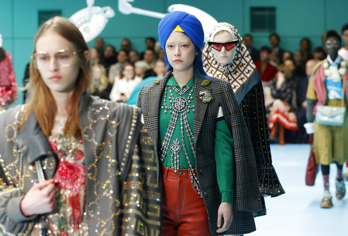 FILE - In this Feb. 21, 2018 file photo, models display items from Gucci's women's Fall/Winter 2018-2019 collection, presented during the Milan Fashion Week, in Milan, Italy. The top civil rights organization for Sikhs in the United States says Nordstrom has apologized to the community for selling an $800 turban they found offensive, but they are still waiting to hear from the Gucci brand that designed it, Saturday, May 18, 2019. (AP Photo/Antonio Calanni, File)