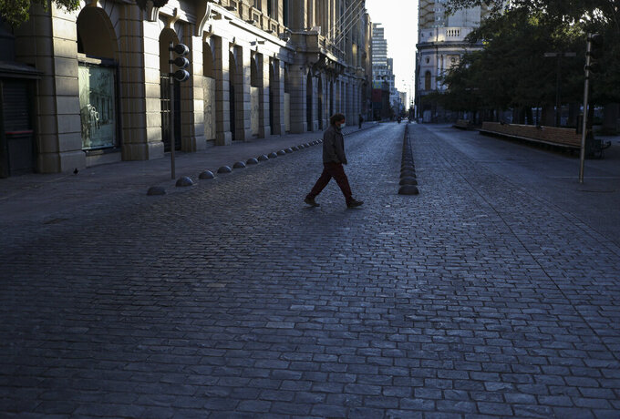A man walk through the iconic Paseo Ahumada usually streaming with pedestrians, during a reinstated lockdown to help contain the spread of COVID-19, in Santiago, Chile, Saturday, March 27, 2021. (AP Photo/Esteban Felix)