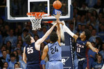 Villanova's Jeremiah Robinson-Earl (24) shoots between Pennsylvania's AJ Brodeur (25) and Lucas Monroe (11) during the first half of an NCAA college basketball game Wednesday, Dec. 4, 2019, in Villanova, Pa. (AP Photo/Matt Slocum)