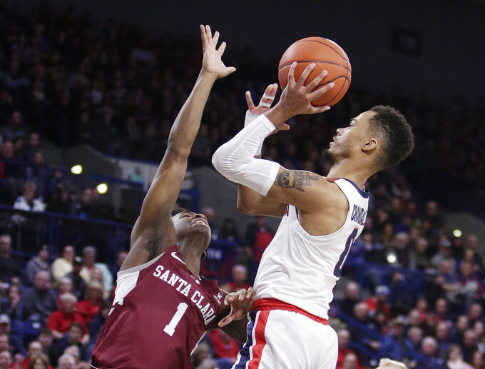 Gonzaga guard Geno Crandall (0) shoots while defended by Santa Clara guard Trey Wertz (1) during the second half of an NCAA college basketball game in Spokane, Wash., Saturday, Jan. 5, 2019. (AP Photo/Young Kwak)