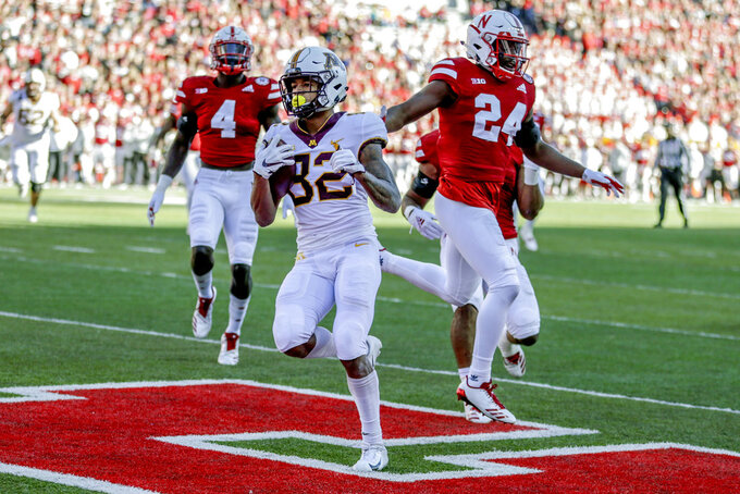 In this Oct. 20, 2018 photo, Minnesota wide receiver Demetrius Douglas (82) scores a touchdown in front of Nebraska defensive backs Avery Anderson (4) Aaron Williams (24), during the first half of an NCAA college football game in Lincoln, Neb. Nebraska's defense goes on the road to face one of the most explosive teams in the nation in No. 8 Ohio State after a middling performance against a mediocre FCS offense in Bethune-Cookman. (AP Photo/Nati Harnik)