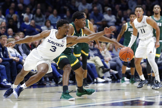 Xavier guard Quentin Goodin (3) and Siena guard Jalen Pickett, center, vie for the ball iduringthe first half of an NCAA college basketball game Friday, Nov. 8, 2019, in Cincinnati. (AP Photo/John Minchillo)
