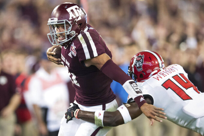 Texas A&M quarterback Kellen Mond (11) is tackled by North Carolina State safety Dexter Wright (14) during the first half of the Gator Bowl NCAA college football game Monday, Dec. 31, 2018, in Jacksonville, Fla. (James Gilbert/The Florida Times-Union via AP)