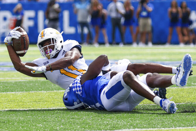 Chattanooga wide receiver Tyron Arnett (11) gets tackled by a Kentucky defender during the second half of a NCAA college football game in Lexington, Ky., Saturday, Sept. 18, 2021. (AP Photo/Michael Clubb)