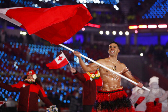 FILE - In this Feb. 9, 2018, file photo, Peta Taufatofua carries a flag of Tonga during the opening ceremony of the 2018 Winter Olympics in Pyeongchang, South Korea, Friday, Feb. 9, 2018. Taufatofua decided to leave his shirt on Tuesday, June 23, 2020 when he led a group of 23 fellow Olympians in a home workout video to help celebrate Olympic Day across 20 time zones. (AP Photo/Jae C. Hong, File)