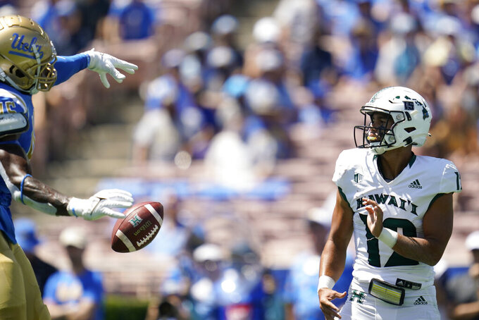 UCLA Bruins linebacker Mitchell Agude (45) blocks a throw by Hawaii Warriors quarterback Chevan Cordeiro (12) during the first half of an NCAA college football game Saturday, Aug. 28, 2021, in Pasadena, Calif. (AP Photo/Ashley Landis)