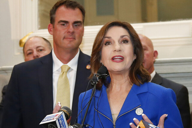 FILE - In this May 16, 2019, file photo, Joy Hofmeister, Oklahoma's State Superintendent of Public Instruction, speaks during a news conference accompanied by Oklahoma Gov. Kevin Stitt, left, in Oklahoma City. Some Oklahoma educators oppose Gov. Stitt's waiver of a mandatory quarantine for public school students, teachers and staff who are exposed to the coronavirus in schools that have a mask mandate. A spokesperson for Hofmeister said Wednesday, Jan. 13, 2021, that Hofmeister did not know about Stitt's plan and was not asked for input. (AP Photo/Sue Ogrocki File)