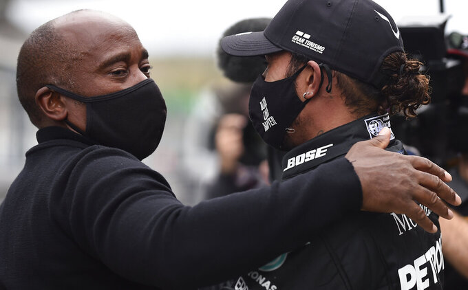 Mercedes driver Lewis Hamilton of Britain is congratulated by his father Anthony Hamilton after his record breaking win during the Formula One Portuguese Grand Prix at the Algarve International Circuit in Portimao, Portugal, Sunday, Oct. 25, 2020. (Jorge Guerrero, Pool via AP)