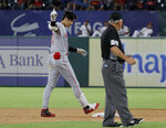 Los Angeles Angels' Shohei Ohtani gestures to the dugout after hitting an RBI double, next to umpire Tom Hallion (20), during the eighth inning of the team's baseball game against the Texas Rangers in Arlington, Texas, Tuesday, Aug. 20, 2019. (AP Photo/Tony Gutierrez)