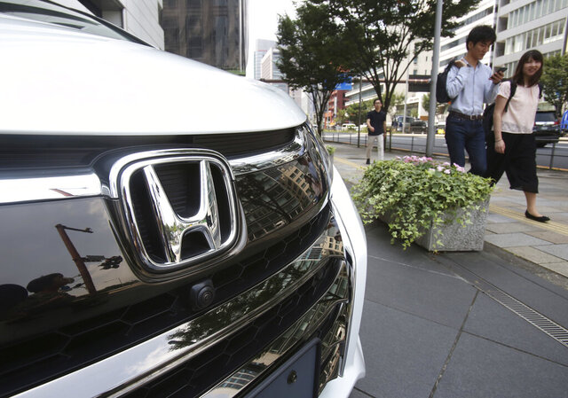 FILE - In this July 31, 2019, file photo, people walk past a Honda car on display at Honda Motor Co. headquarters in Tokyo. Japanese automaker Honda reported Wednesday, Aug. 5, 2020, it sank into the red for the April-June quarter, as its sales plunged over the coronavirus pandemic, especially in the U.S., Japan and India. (AP Photo/Koji Sasahara, File)