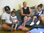 Jose Serrano, husband of Zeneida Torres, plays with J.T, 18 months as Zeneida Torres talks and four year old Jacob plays. Zeneida Torres, of Bethlehem lost her sister Jackie to COVID-19 in December, Tuesday, Aug. 31, 2021 in Bethlehem, Pa. Torres adopted Jackie's sons, ages 4, 18 months and 8 months, all of whom have special needs. (April Gamiz/The Morning Call via AP)