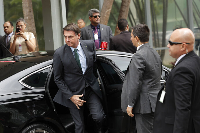 Brazil's President Jair Bolsonaro exits his car for a meeting with military commanders at the Defense Ministry in Brasilia, Brazil, Tuesday, Jan. 7, 2020. Bolsonaro spoke about maintaining commercial ties with Iran this morning, saying he would speak to his foreign minister about talks with Iran and reiterated that Brazil opposes terrorism. (AP Photo/Eraldo Peres)