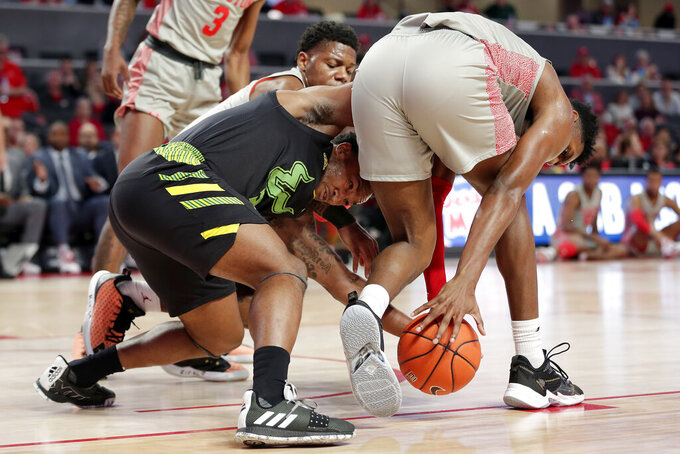 South Florida guard Laquincy Rideau, left, dives into the scrum to recover the ball with Houston guard Marcus Sasser, back, and center Chris Harris Jr., right, during the first half of an NCAA college basketball game Sunday, Jan. 26, 2020, in Houston. (AP Photo/Michael Wyke)