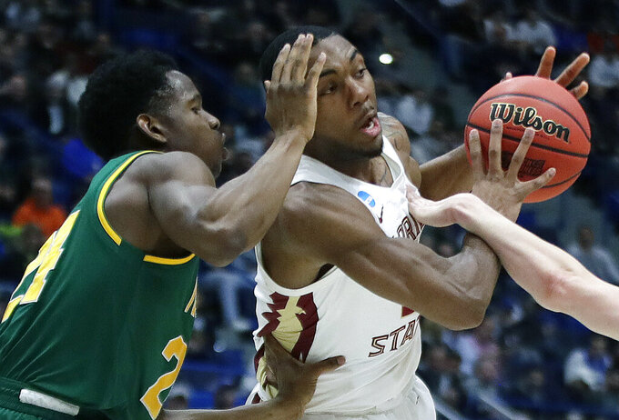 Florida State's Trent Forrest, right, makes a move against Vermont's Ben Shungu (24) during the first half of a first round men's college basketball game in the NCAA Tournament, Thursday, March 21, 2019, in Hartford, Conn. (AP Photo/Elise Amendola)