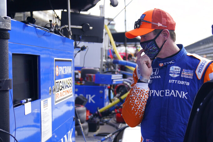 Scott Dixon, of New Zealand, looks at the results from a practice session for an IndyCar auto race at Indianapolis Motor Speedway, Thursday, Oct. 1, 2020, in Indianapolis. (AP Photo/Darron Cummings)