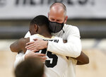 Colorado coach Tad Boyle, back, hugs guard McKinley Wright IV as Wright was introduced as one of the team's graduating seniors, following the team's NCAA college basketball game against UCLA on Saturday, Feb. 27, 2021, in Boulder, Colo. (AP Photo/David Zalubowski)