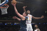 Denver Nuggets center Nikola Jokic (15) goes to the basket past New York Knicks guard Frank Ntilikina (11) during the first half of an NBA basketball game Friday, March 22, 2019, at Madison Square Garden in New York. (AP Photo/Mary Altaffer)