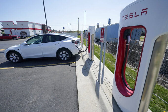 A Tesla charges at a station in Topeka, Kan., Monday, April 5, 2021. The president and the auto industry maintain the nation is on the cusp of a gigantic shift to electric vehicles and away from liquid-fueled cars, but biofuels producers and some of their supporters in Congress aren't buying it. They argue the U.S. should increase sales of ethanol and biodiesel, not abandon them. (AP Photo/Orlin Wagner)