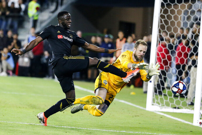 FILE - In this Oct. 29, 2019, file photo, Seattle Sounders goalkeeper Stefan Frei, right, makes a save against Los Angeles FC forward Adama Diomande during the second half of an MLS soccer Western Conference final in Los Angeles. Diomande has announced he is leaving LAFC. The club did not immediately respond to Diomande's posts on social media. (AP Photo/Ringo H.W. Chiu, File)