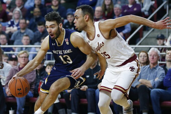 Notre Dame's Nikola Djogo (13) drives past Boston College's Jordan Chatman (25) during the second half of an NCAA college basketball game in Boston, Saturday, Feb. 2, 2019. (AP Photo/Michael Dwyer)