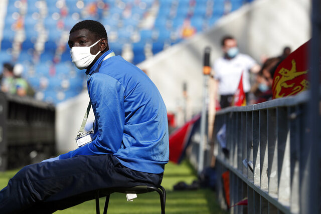 A ball carrier wears a face mask prior to the friendly soccer match between Paris Saint Germain and Le Havre, in Le Havre, western France, Sunday, July 12, 2020. For the first time since the coronavirus shut down sports and chased away spectators, Neymar, Kylian Mbappe and other soccer stars are going to play again in front of fans. (AP Photo/Thibault Camus)