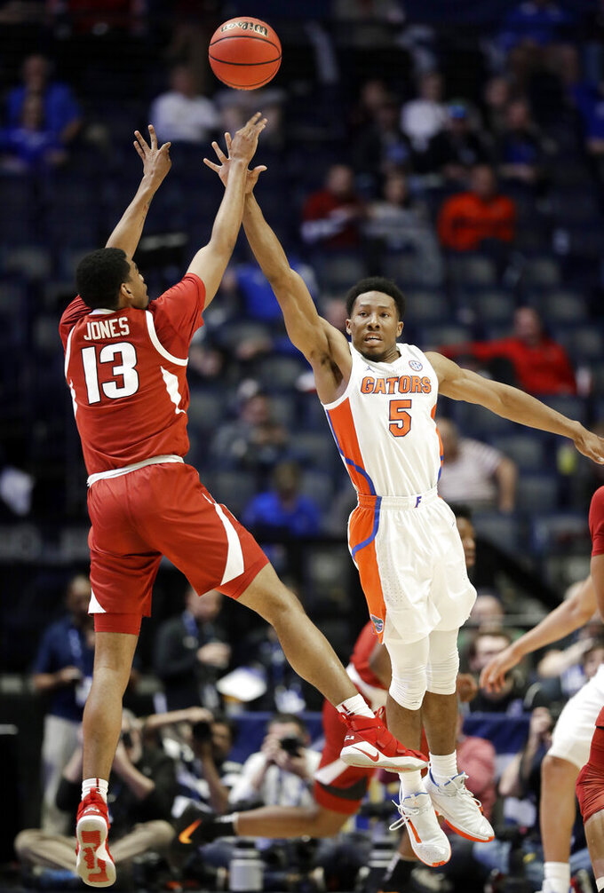 Arkansas guard Mason Jones (13) shoots over Florida's KeVaughn Allen (5) in the second half of an NCAA college basketball game at the Southeastern Conference tournament Thursday, March 14, 2019, in Nashville, Tenn. Florida won 66-50. (AP Photo/Mark Humphrey)
