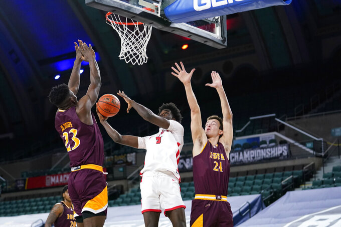 Fairfield's Supreme Cook, center, goes up for a shot between Nelly Junior Joseph, left, and Dylan van Eyck in the second half of an NCAA college basketball game during the finals of the Metro Atlantic Athletic Conference tournament, Saturday, March 13, 2021, in Atlantic City, N.J. (AP Photo/Matt Slocum)