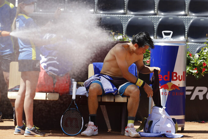 Japan's Kei Nishikori changes his shirt during a match against Italy's Fabio Fognini at the Italian Open tennis tournament, in Rome, Monday, May 10, 2021. (AP Photo/Gregorio Borgia)