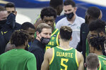 Oregon head coach Dana Altman, center, talks to his players prior the first half of an NCAA college basketball game against Seton Hall in Omaha, Neb., Friday, Dec. 4, 2020. (AP Photo/Kayla Wolf)