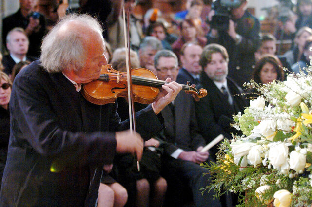 FILE - In this April 3 2004, Israeli violinist Ivry Gitlis, ambassador to the UNESCO, plays at the funeral ceremony of Oscar-winning British actor and play-writer, Sir Peter Ustinov, in the cathedral St. Pierre, in Geneva, Switzerland. Ivry Gitlis, an acclaimed violinist who played with famed conductors, rock stars and jazz bands around the world and worked to make classical music accessible to the masses, has died in Paris at 98. (Martial Trezzini/Pool Photo via AP, File)